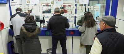 Varios clientes compran en una administración de lotería.