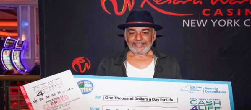 El agraciado posa con su cheque ganador.
