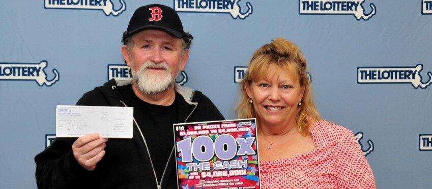 La pareja de agraciados posa con el cheque millonario. Foto: Lotería de Massachusetts.