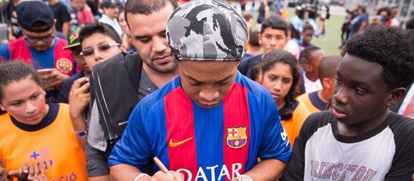 Ronaldinho firma autógrafos a un grupo de aficionados. Foto: Twitter.